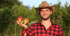 Young Peasant Farmer Man Holding Two Bio Mango Fruits and Smiling in Farm Garden Stock Footage