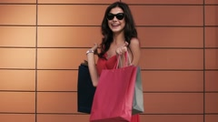Fair-skinned young woman spin her shopping bags around Stock Footage