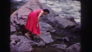 1958: hiking women in formal red dress sits by fast flowing river water COLORADO Stock Footage