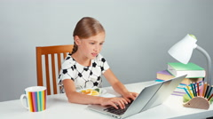 Schoolgirl using her laptop and playing with sweets sitting at the desk Stock Footage