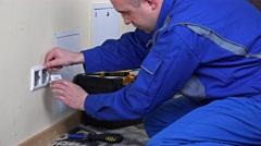 Electrician man installing a wall power socket Stock Footage