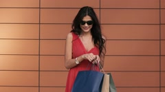 Attractive young woman looking into her shopping bag shines with happiness Stock Footage