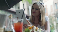 Happy businesswoman having a break in the outdoor cafe and browsing internet on  Stock Footage