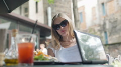 Businesswoman wearing sunglasses and reading documents in the outdoor cafe Stock Footage