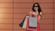 Portrait of beautiful young brunette girl holding shopping bags Stock Footage
