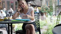 Businesswoman working on papers and having a call in the outdoor cafe, steadycam Stock Footage
