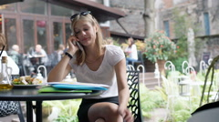 Worried businesswoman sitting in the outdoor cafe and talking about outcomes Stock Footage