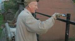 Worker painting the iron fence using black paint Stock Footage