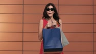 Pretty brunette with shopping bags points her finger at the camera Stock Footage