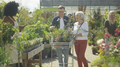4K Customers shopping in plant nursery & friendly worker with tablet computer Stock Footage