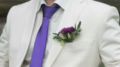 The groom dressed in a white suit with purple tie Stock Footage