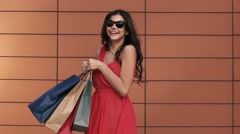 Coquette young woman turns around with the shopping bags. Slow motion Stock Footage