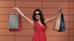 Beautiful fair-skinned smiling girl holding shopping bags high. Slow motion Stock Footage