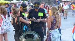 2 policemen writing a ticket to teenagers girl, crowed square during festival Arkistovideo