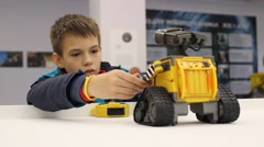 Kid playing with WALL-E. Robot toy character form WALL-E animation film by Disne Stock Footage