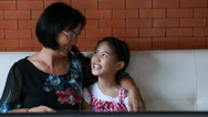 4K : Asian senior woman with little girl watching TV on sofa together Stock Footage