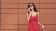 Cheerful young woman with shopping bags talking on the phone Stock Footage