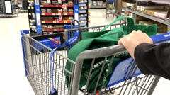 Woman pushing trolley to buy goods at Walmart during the busy holiday season Stock Footage