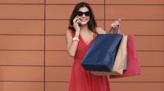 Excited young woman holding shopping bags and talking on the phone Stock Footage