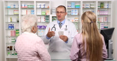 Old and Young Women Pharmacy Client Pharmacist Man Pill Drug Presentation Advice Stock Footage