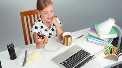 School girl 7-8 years eating sandwich with butter and jam sitting at the desk Stock Footage