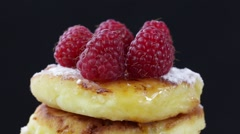 Rotation healthy homemade cheese pancakes with raspberry on black background Stock Footage