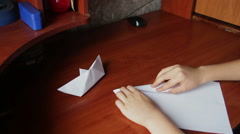 Children's hands making origami plane Stock Footage