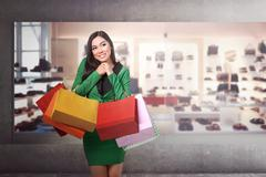 Young pretty asian girl standing in front of a store Stock Photos