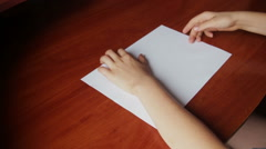 Children's hands making origami ship Stock Footage