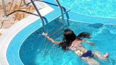 Young girl swimming and goes the stairs to exit the pool. 4k aerial shot Stock Footage