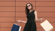 Fair-skinned beautiful girl turns shopping bags enjoying her purchases Stock Footage