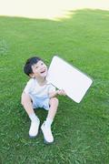 Japanese young boy with whiteboard in a city park Stock Photos