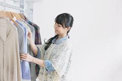 Young woman with long hair choosing clothes in a walk in closet Stock Photos