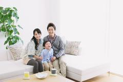 Young adult couple and their son on the sofa smiling at camera Stock Photos