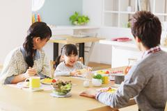 Young adult couple and their daughter having breakfast in their dining room Stock Photos