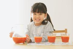 Elementary age girl pouring tomato juice into glasses Stock Photos