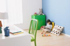 Elementary age girl reading an illustrated book on the floor of the kids room Stock Photos