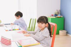 Elementary age brother and sister doing homework at their desk Stock Photos