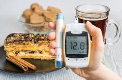Diabetes and unhealthy eating concept. Hand holds glucometer and sweets and c Stock Photos