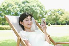 Japanese woman with smartphone on deck chair in a city park Stock Photos