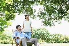 Happy Japanese couple with deck chair in a park Stock Photos