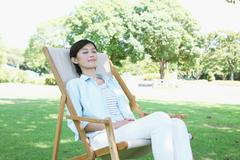 Japanese woman resting on deck chair in a city park Stock Photos