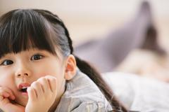 Close up of elementary age girl lying on the floor and looking at camera Stock Photos