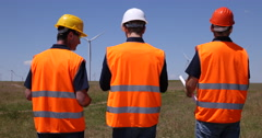 Electric Tower Worker Men Walking Wind Turbine Field Discussing Power Generation Stock Footage