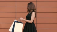 Happy shopping woman looking cheerfully into her shopping bag. Slow motion Stock Footage