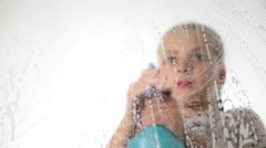 Close-up smiling little housewife washed the window with a spray, cloth and Stock Footage