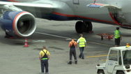 Airport worker in green overalls closes the cargo compartment of the aircraft Stock Footage