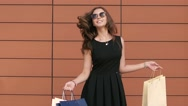 Beautiful fair-skinned girl enjoying her purchases waves her hair. Slow motion Stock Footage