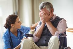 Nurse taking care of sad senior man in a retirement home Kuvituskuvat