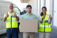 Portrait of workers are posing with thumbs up close to a delivery man Stock Photos